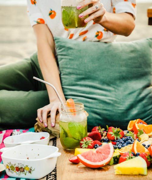 Woman sitting on picnic blanket eating a fruit salad.
